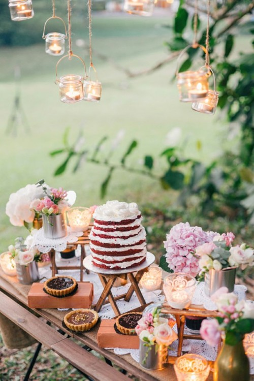 a summer weddign dessert table with pendant candle lanterns, pink blooms and greenery, pies and cakes on stands and folding stands