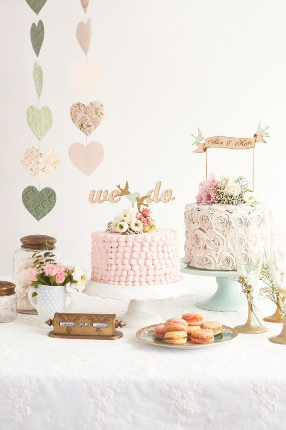 a chic vintage wedding dessert table with pastel heart banners, pink and white blooms and greenery, pink cakes and macarons