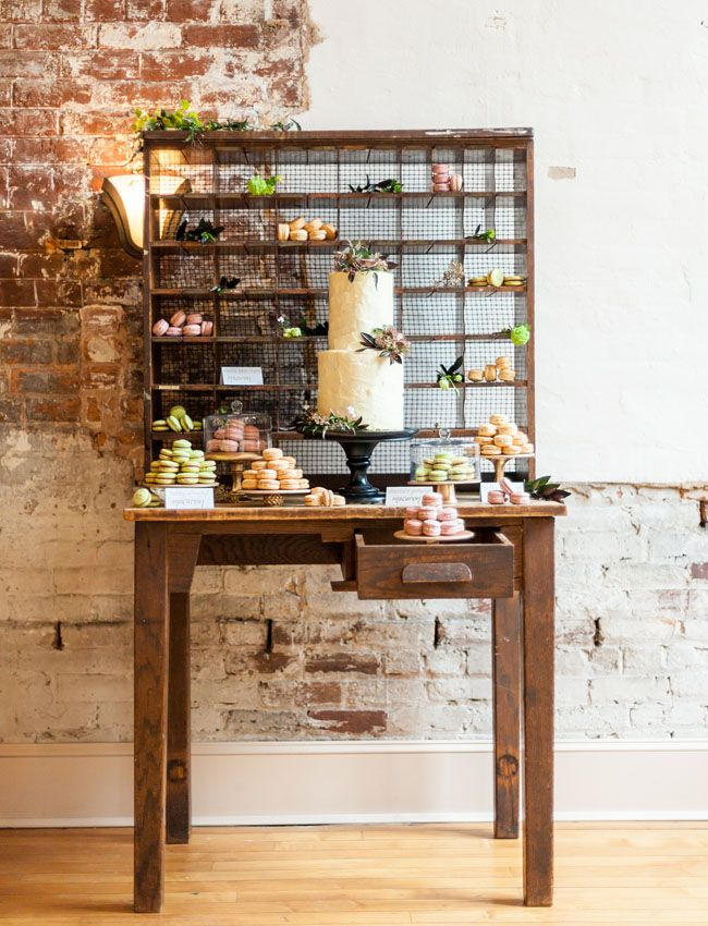 a rustic dessert table with a stand with bright macarons, blooms and greenery and a cake on a chic black stand