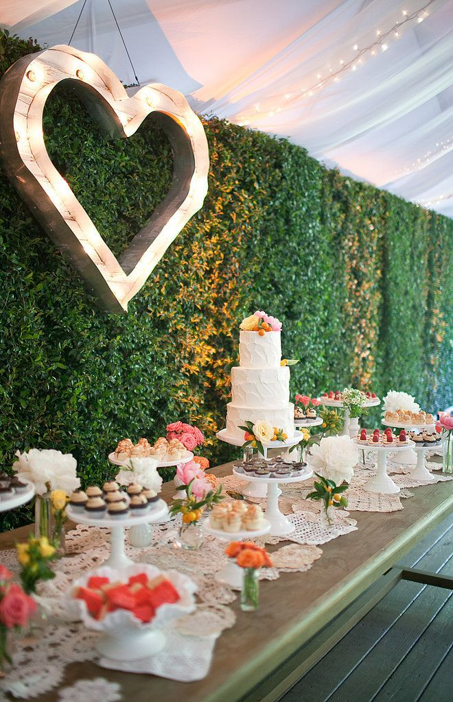 a rustic table with a doliy runner, a green living wall as a backdrop and a marquee heart on the wall