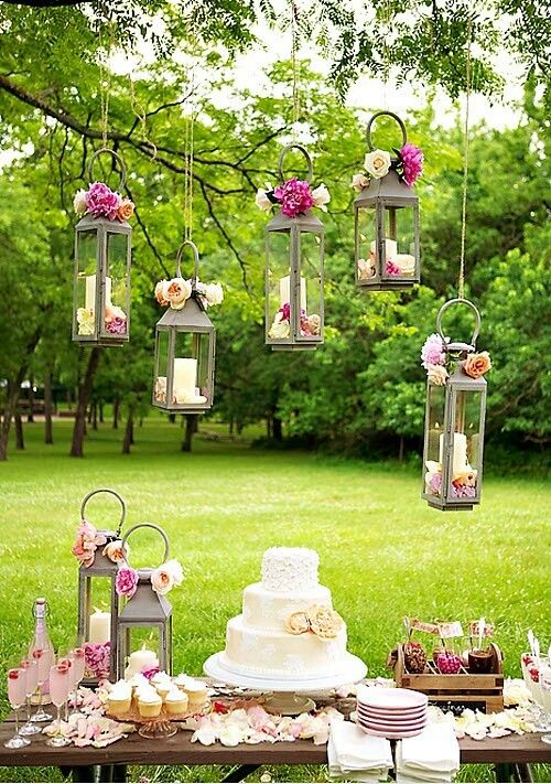 a chic garden wedding dessert table with hanging candle lanterns with pink blooms, pink lemonade, flowers and sweets