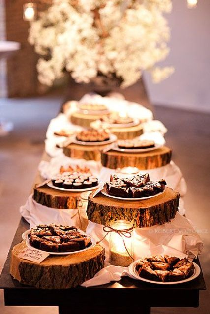 a rustic dessert table with candles and wood slice stands plus pendant lamps to accent the table a lot