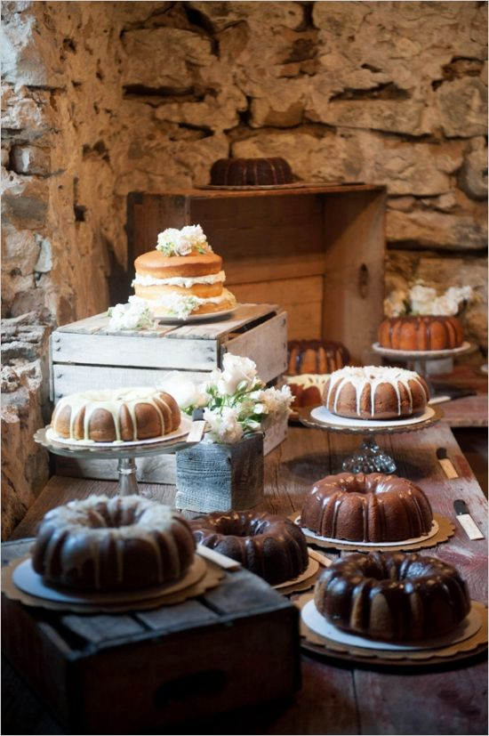 a rustic wooden dessert table with crates and a variety of bundt cakes and naked ones plus blooms around