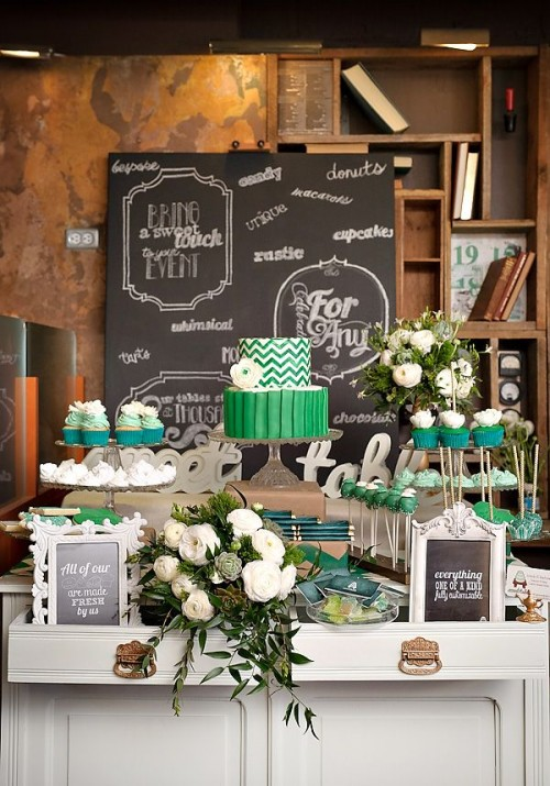 a bright green or emerald wedding dessert table with white flowers and greenery and tall stands for yummies