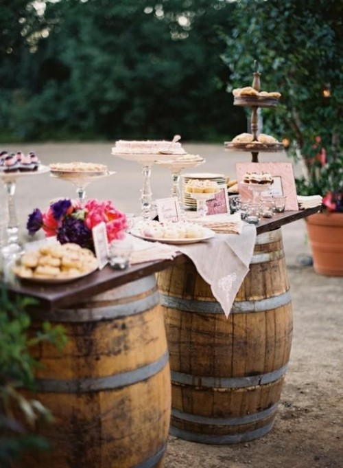 a vineyard wedding dessert table with barrels and bright flowers plus silver stands and glass ones