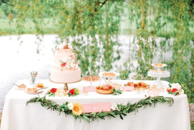 a summer dessert table with greenery and bright flowers and bright desserts and cakes topped with flowers