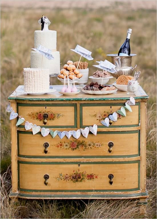 a rustic wedding dessert table with a paper banner, sweets with toppers and some champagne in a bucket