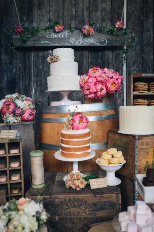 a rustic wedding dessert table organized on wooden crates and barrels, with bright blooms and white porcelain for sweets