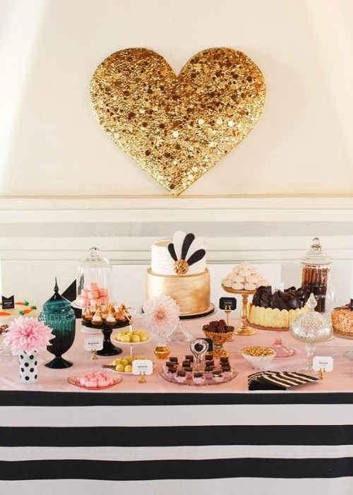 a chic dessert table in black and white stripes, with a pink countertop plus a gold sequin heart over it for more romance