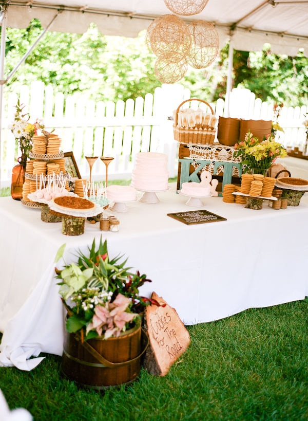 a white dessert table covered with a tablecloth, with pink blooms and greenery, wicker lamps and baskets for holding food