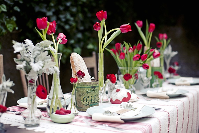 a relaxed summer tablescape with a striped tablecloth, bright red tulips and pale greenery in vases