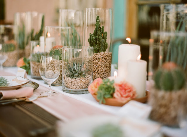 a summer wedding tablescape done with potted cacti, candles and peachy blooms plus light pink linens