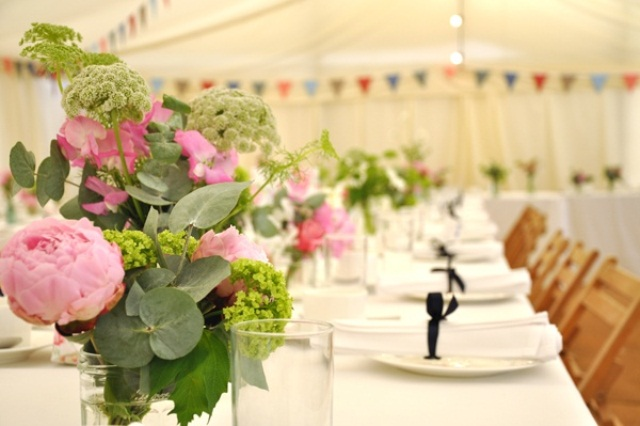 a summer wedding table done with bright pink blooms and greenery is a chic and bold idea to rock