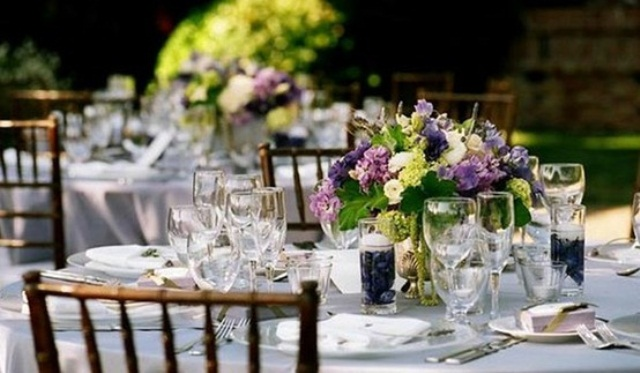 a neutral wedding table with purple and green blooms and candles looks chic and stylish