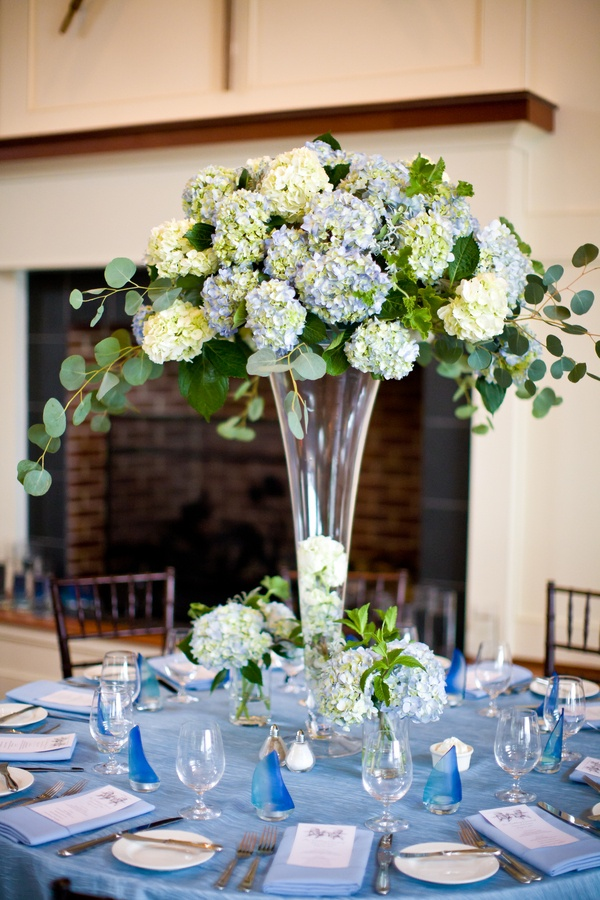 a beautiful summer wedding tablescape with a blue tablecloth, blue linens and lush blue and white oversized floral centerpiece