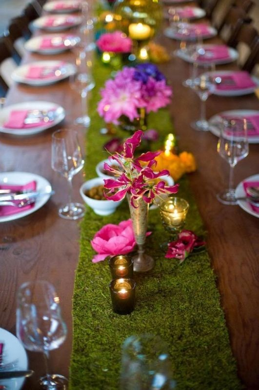 a summer wedding tablescape with a moss table runner, bright blooms, candles and purple linens