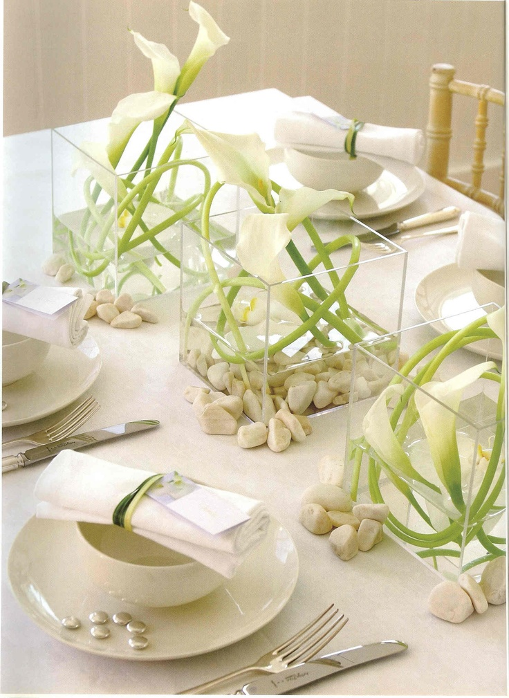 a neutral summer wedding tablescape with white florals in square vases, with neutral linens, simple porcelain and cutlery