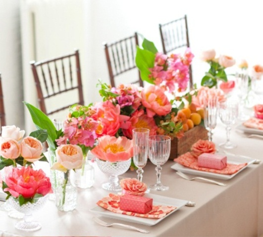 a colorful and refreshing summer wedding table with bright florals, greenery and some fruit plus colorful napkins and favor boxes