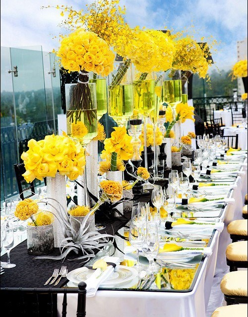 a contrasting summer wedding tablescape done in black, white and yellow, with statement florals, a black runner and neutral napkins