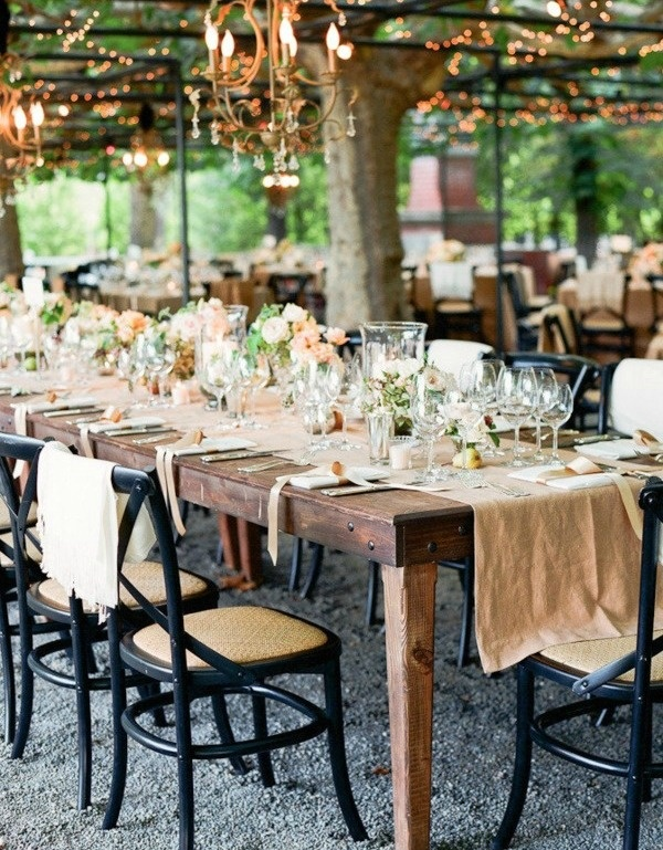 a rustic summer wedding tablescape with a burlap runner and neutral linens, pastel and white blooms and gorgeous crystal chandeliers over the space