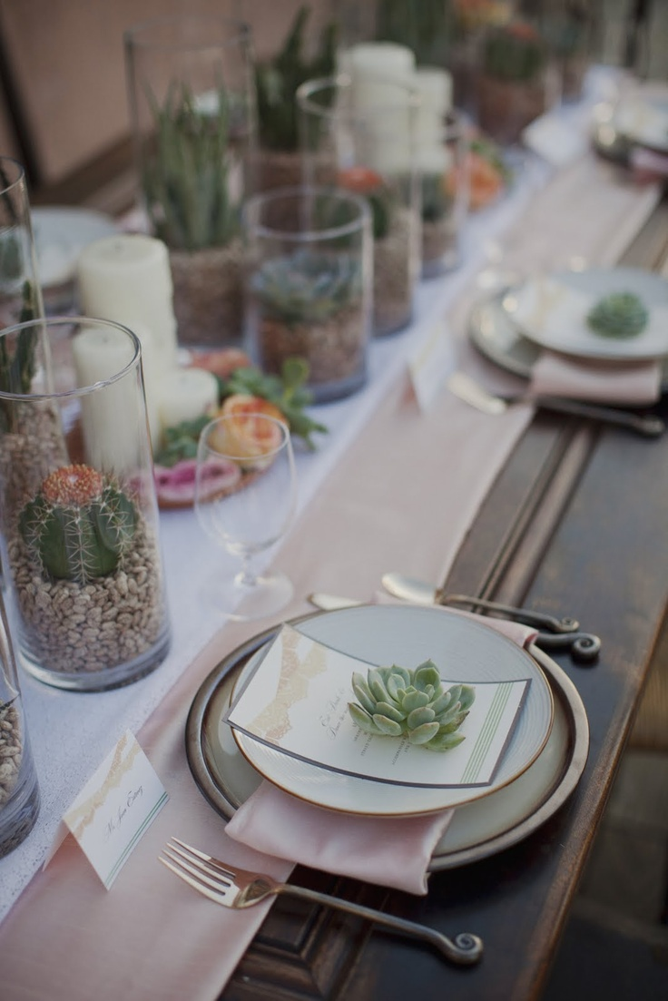 a chic neutral wedding tablescape with layered table runners, succulents in pots, candles and simple plates