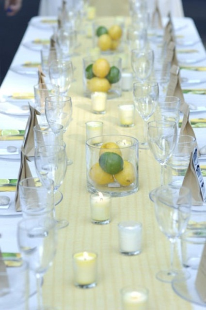 a bright summer wedding table with a printed yellow table runner, fruit centerpieces and candles and all neutral everything