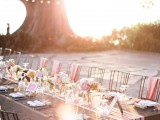 a relaxed and bright summer wedding tablescape with pink linens, pink blooms, a striped table runner is cute and feels like summer