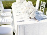 a chic white summer wedding tablescape with a textural tablecloth, lush white orchids and simple linens and cutlery with a sea view