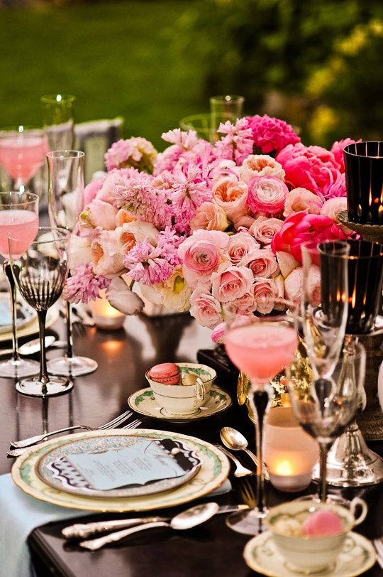 an exquisite bright summer wedding tablescape with super lush pink florals, candles and macarons