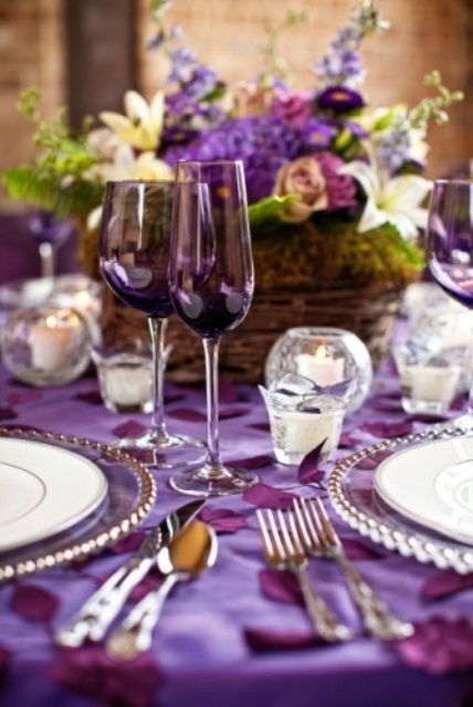 a colorful summer wedding tablescape with purple linens, purple and neutral blooms in moss, candles and purple glasses