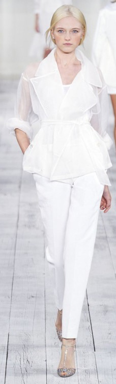 an ethereal white pantsuit with a top, white pants, a sheer jacket with long sleeves and silver heels for a modern casual bride