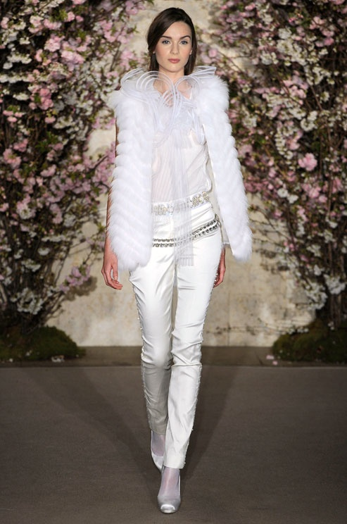a whimsical bridal suit with a semi sheer top, white silk pants, a white faux fur coverup and white shoes