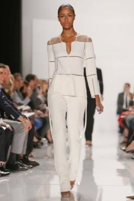 a chic white pantsuit with white pants, a sculptural white and sheer top with long sleeves for a retro-inspired look