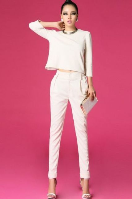 a retro-inspired bridal pantsuit with pants and a simple long sleeve top, white heels and a shiny glam clutch
