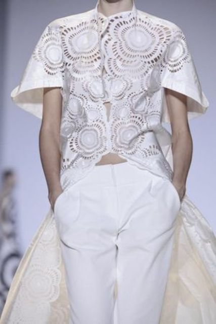 a whimsical bridal pantsuit with white palazzo pants and a cut out oversized top with short sleeves and a train