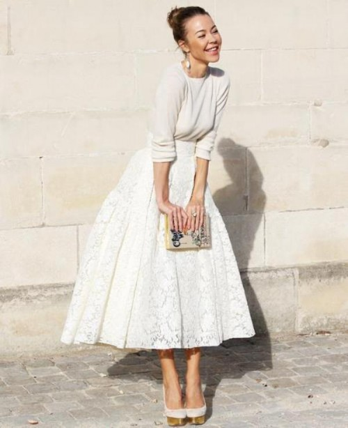 a neutral long sleeve top, a white a-line lace midi skirt, white shoes and a whimsical clutch for a casual fall or winter bridal look