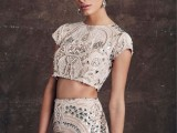 a refined blush bridal separate with embellishments, a crop top with a high neckline and short sleeves and a fitting skirt