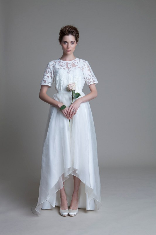 a white lace top with a high neckline and short sleeves, a layered high low skirt with a train for a romantic and chic look