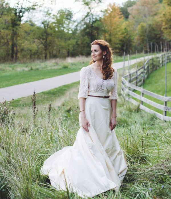 a lovely vintage inspired bridal look with a lace top with a deep neckline and long sleeves and a plain skirt decured with a thin belt is gorgeous