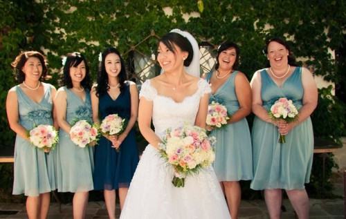 aqua midi dresses with fabric flowers for the bridesmaids and a teal gown for the maid of honor