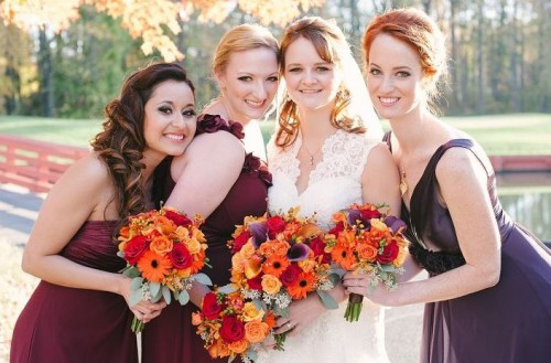 mismatching burgundy dresses for the bridesmaids and a purple gown for the maid of honor