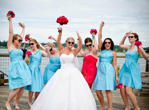 mismtaching light blue bridesmaid dresses and a strapless red one for the maid of honor