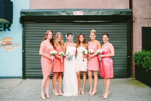 mismatching coral pink over the knee bridesmaid dresses and a strapless draped ivory one for the maid of honor