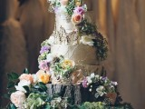 a woodland wedding cake that seems to be covered with birch bark, fresh blooms and berries and presented on a wood slice plus florals and moss