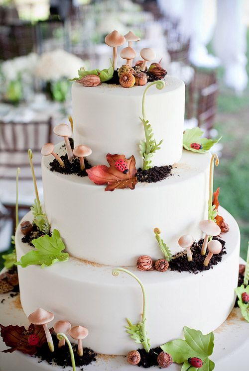 a whimsy woodland wedding cake in pure white decorated with edible dirt, mushrooms, greenery and even insects
