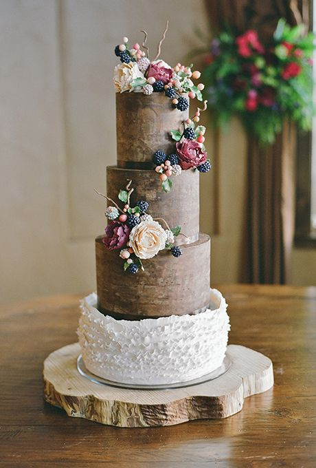a gorgeous woodland wedding cake, partlychocolate and partly with white ruffles, with edible berries, greenery and branches