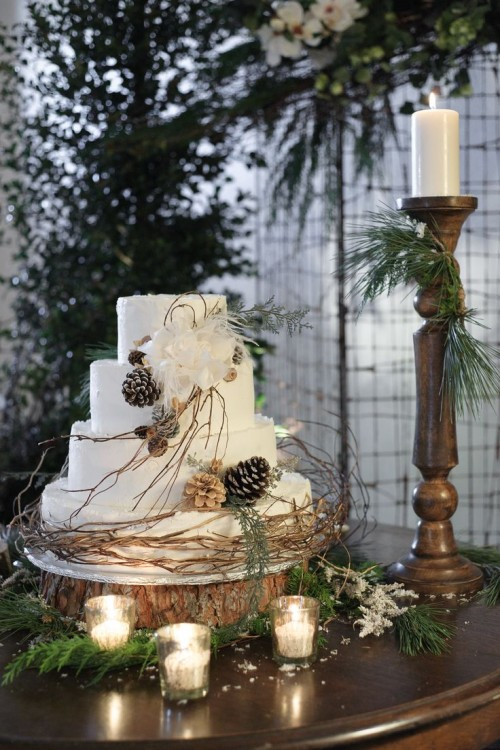 a cozy rustic wedding cake in white, with branches, pinecones and foliage and faux blooms