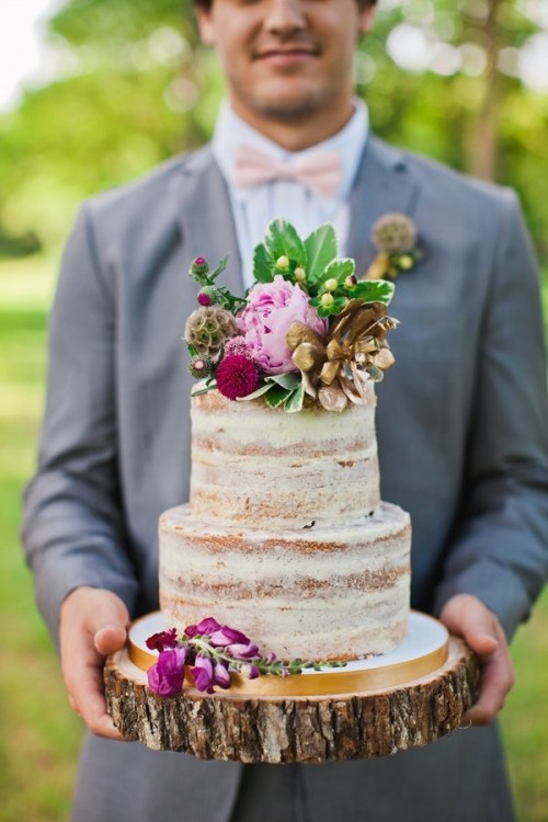 a naked wedding cake topped with fresh blooms, berries and greenery for a woodland wedding