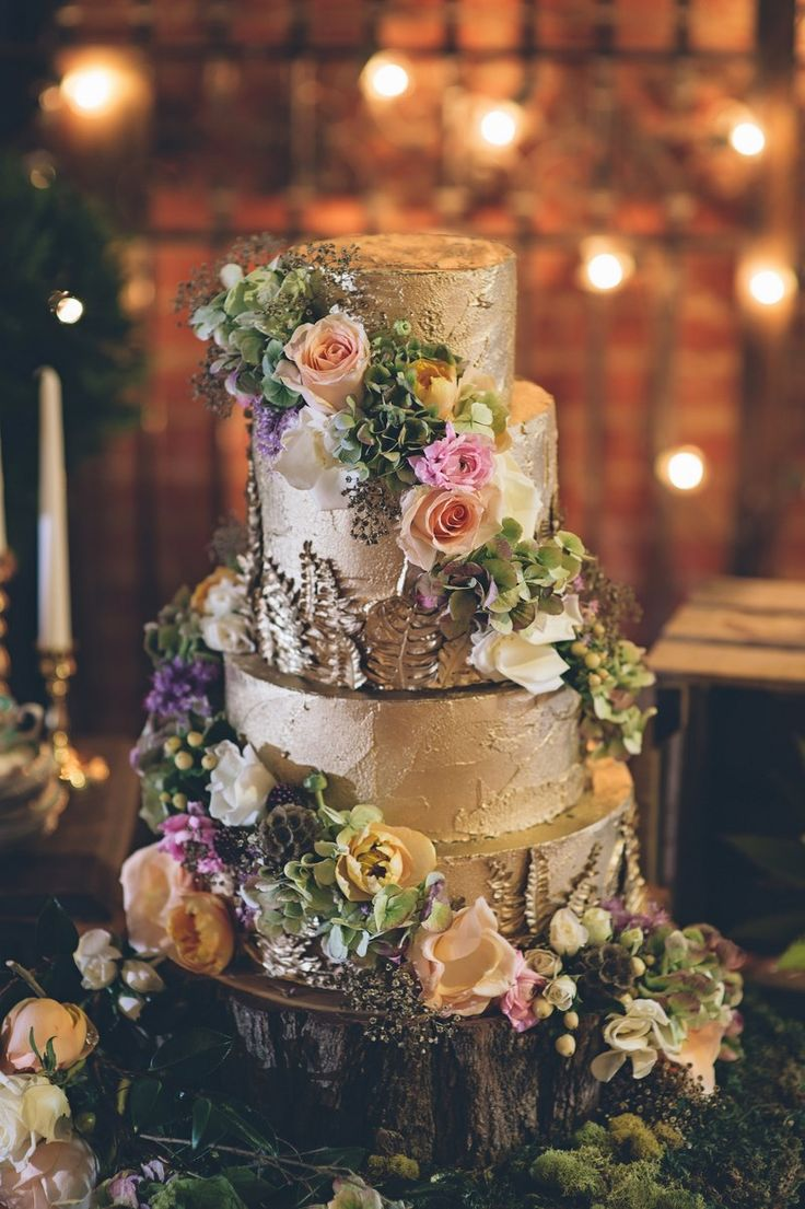 a fantastic woodland wedding cake with textural buttercream, colored blooms, greenery placed on a wood slice