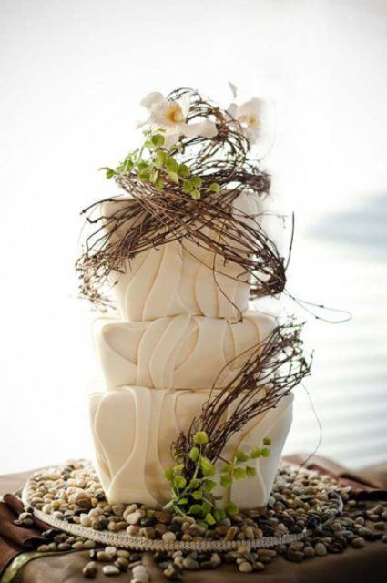 a whimsical woodland wedding cake with textural buttercream, branches, greenery and white blooms on top